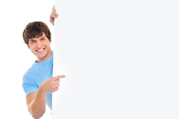 Gelukkig lachend knappe man kijken uit van banner en aangeven met de vinger erop Gratis Foto