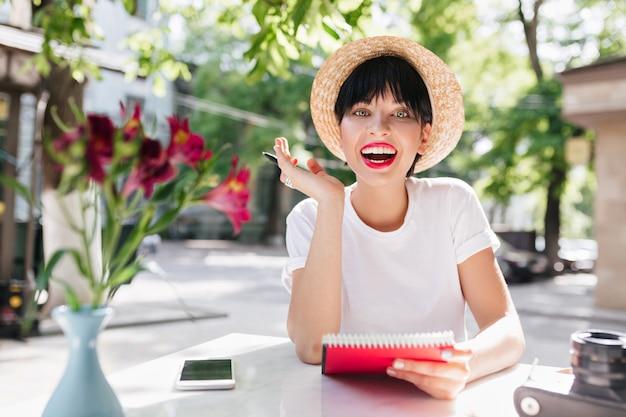 Gelukkig lachend meisje met kort zwart haar had een geweldig idee, zittend met notitieboekje en pen in de groene tuin Gratis Foto