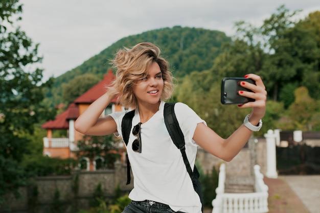 Gelukkig lachend reiziger meisje met krullend kapsel selfie maken over berg. reiziger die in vrouwelijke handmobiel gebruikt. toeristische blik op berg, zomerlevensstijl Gratis Foto