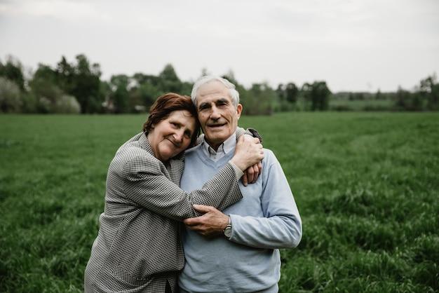 Gelukkig lachend senior paar verliefd op de natuur, plezier maken. bejaarde echtpaar op het groene veld. leuke senior paar wandelen en knuffelen in voorjaar bos Premium Foto
