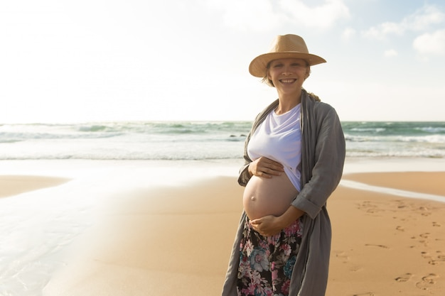 Gelukkig lachend zwangere vrouw hand in hand op buik Gratis Foto