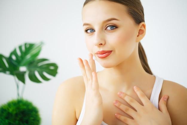 Gelukkig lachende jonge vrouw met perfecte huid, natuurlijke make-up en een mooie glimlach. Premium Foto