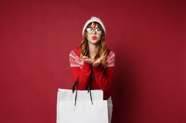 Gelukkig langharige vrouw in winterkleren met boodschappentassen Gratis Foto