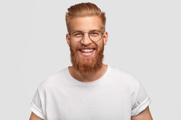 Gelukkig man met lange dikke gemberbaard, heeft een vriendelijke glimlach Gratis Foto