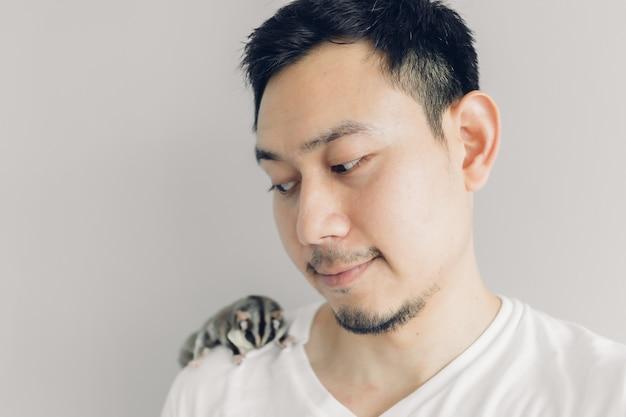 Gelukkig man neemt selfie van zichzelf en zijn huisdier sugar glider. Premium Foto
