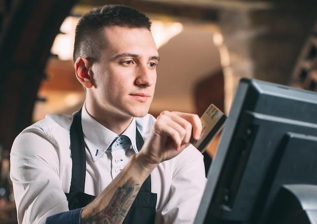 Gelukkig man of ober in schort aan balie met kassa werken bij bar of coffeeshop Premium Foto