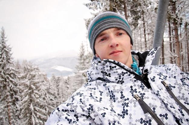 Gelukkig man stijgt op de lift in de karpaten. detailopname. winter natuur. er valt zware sneeuw. Premium Foto