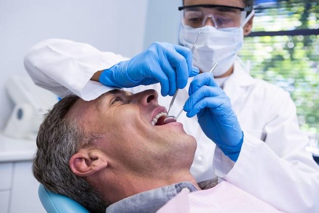 Gelukkig man tandheelkundige behandeling door tandarts Premium Foto