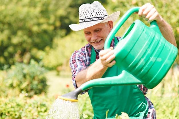 Gelukkig man zijn planten water geven in de zomer Gratis Foto