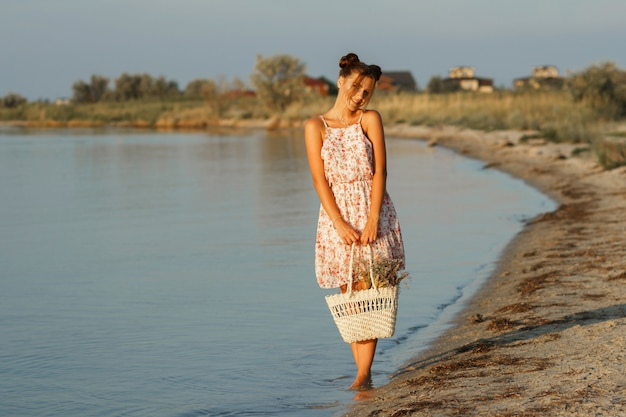 Gelukkig meisje bij zonsondergang aan zee met een strozak en een hoed gaat op blote voeten. de achtergrond is wazig. Premium Foto
