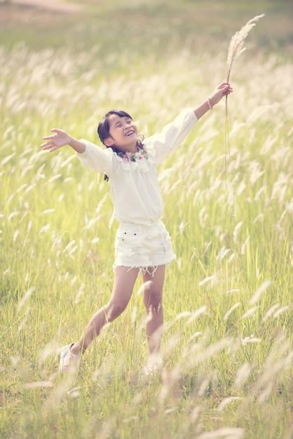 Gelukkig meisje dat en in het park loopt speelt Premium Foto