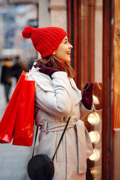 Gelukkig meisje dat grote winkeldisplay bekijkt Gratis Foto