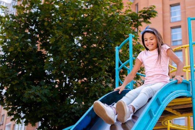 Gelukkig meisje dat op een dia in een speelplaats glijdt Gratis Foto