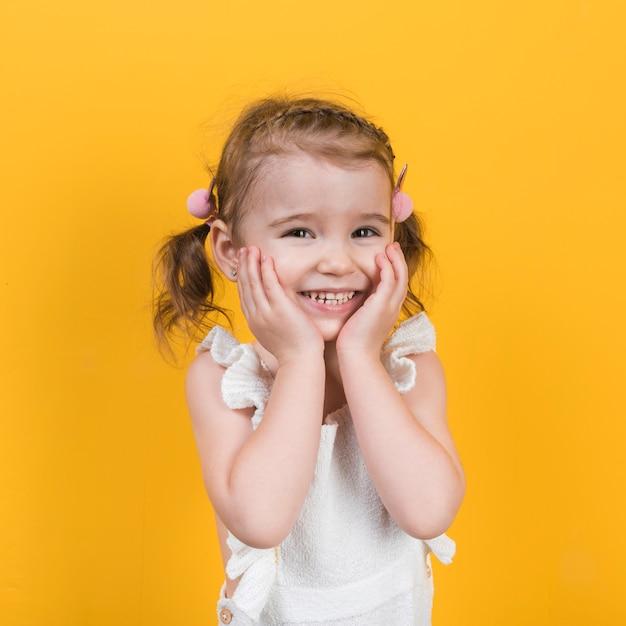 Gelukkig meisje dat op gele achtergrond glimlacht Gratis Foto
