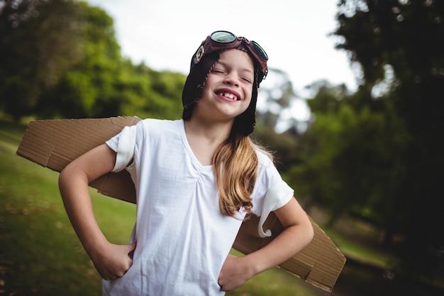 Gelukkig meisje dat zich in het park met hand op heup bevindt Premium Foto