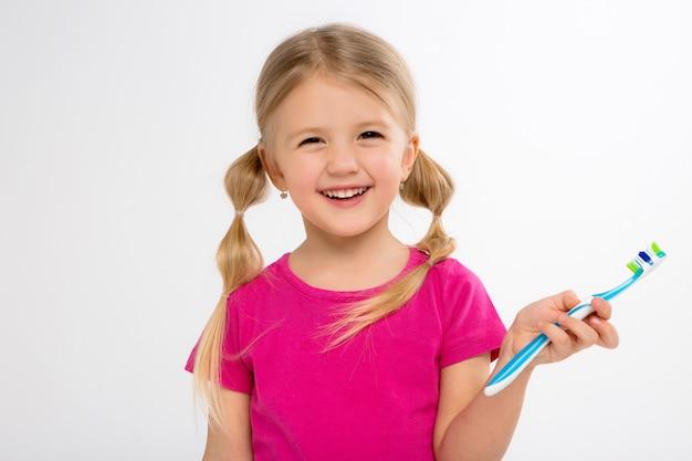 Gelukkig meisje dat zich met tandenborstel bevindt die op wit wordt geïsoleerdl. het weinig kind borstelt zijn tanden. Premium Foto