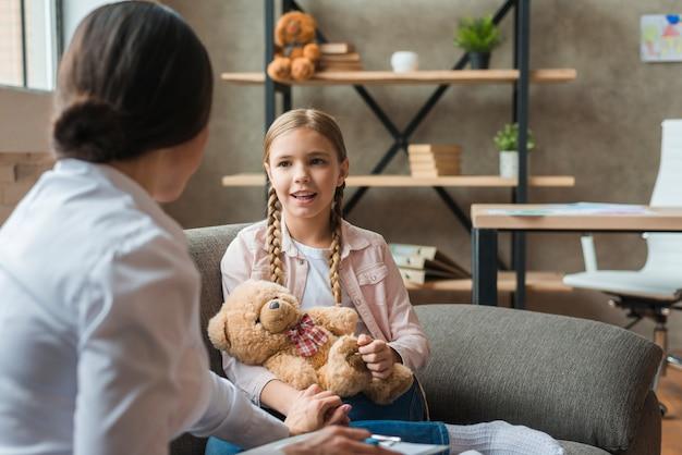 Gelukkig meisje die aan de vrouwelijke psycholoog thuis spreken Gratis Foto