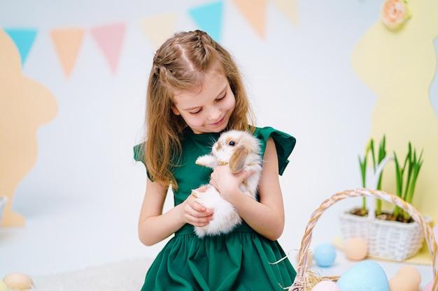 Gelukkig meisje die leuke pluizige konijntjes dichtbij geschilderde paaseieren houden Premium Foto