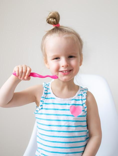 Gelukkig meisje haar tanden, roze tandenborstel, tandhygiëne, ochtendnacht gezonde concept levensstijl borstelen Premium Foto