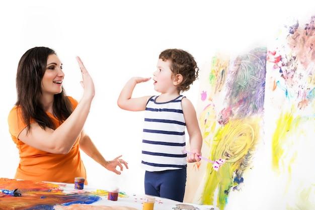 Gelukkig meisje in geel t-shirt en kleine jongen in gestreept shirt geven high five Premium Foto