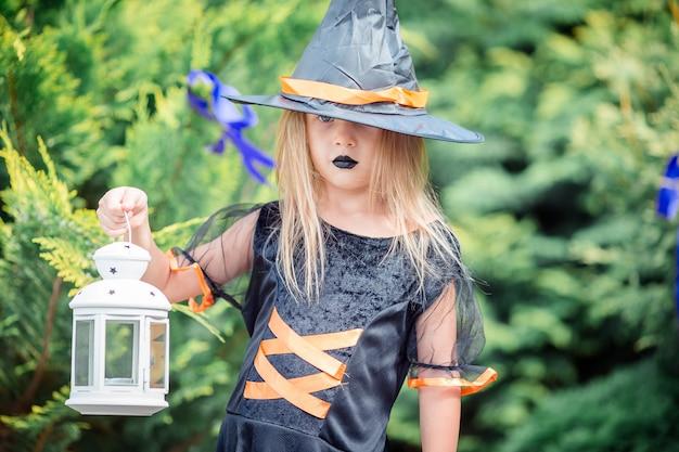 Gelukkig meisje in halloween-kostuum met hefboompompoen kerstmis of behandel Premium Foto