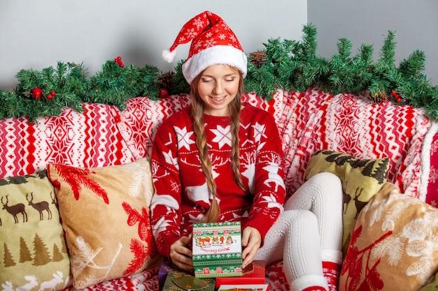 Gelukkig meisje in kerstman hoed opent een kerstcadeau doos met heden binnen Premium Foto