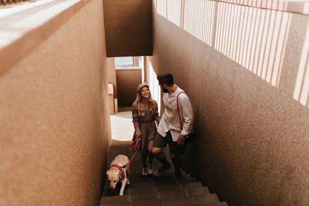 Gelukkig meisje in pet en bruine jurk en haar vriend lopen glimlachend de trap op, van plan om hun hond uit te laten. Gratis Foto