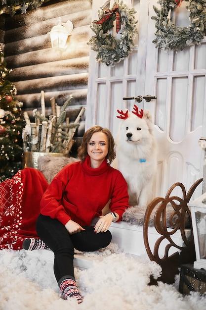 Gelukkig meisje in rode nieuwjaarstrui en scandinavische sokken zit op de trap en poseren met schattige sneeuwwitte samojeed-hond bij kerstinterieur. concept van nieuwjaarsfeest en decoraties Premium Foto