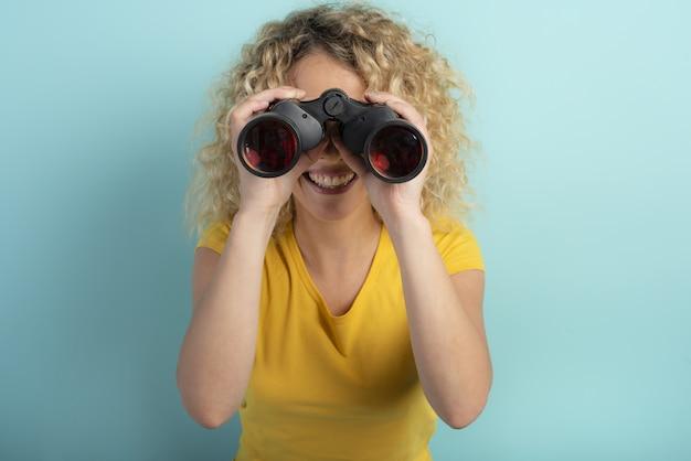 Gelukkig meisje kijkt met verrekijker iets. cyaan muur Premium Foto