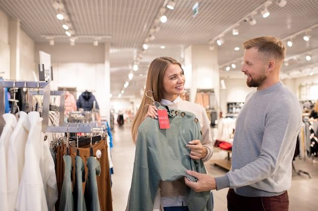 Gelukkig meisje kijkt naar haar vriendje terwijl wijzend op grijze gebreide pullover op hanger bij de borst tijdens het winkelen in het winkelcentrum Premium Foto