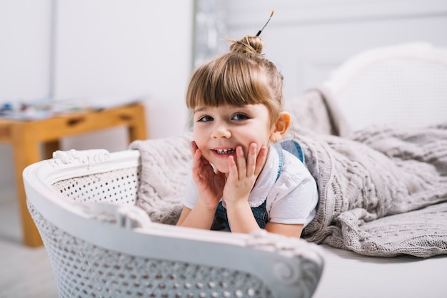Gelukkig meisje liggend op de bank onder deken Gratis Foto