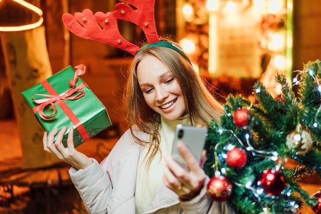 Gelukkig meisje met een kerstboom en een cadeau in haar handen praat en glimlacht aan de telefoon Premium Foto