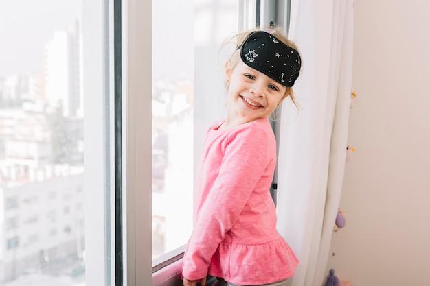 Gelukkig meisje met slaapoogmasker die zich dichtbij glasvenster bevinden Gratis Foto