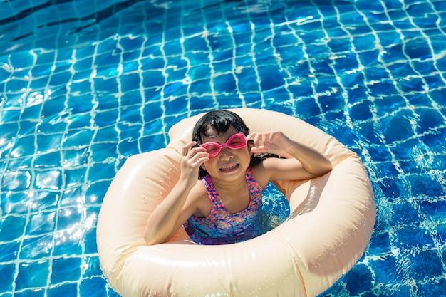 Gelukkig meisje ontspannen met kleurrijke opblaasbare ring in buitenzwembad op warme zomerdag Premium Foto