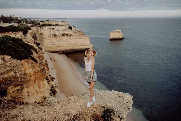 Gelukkig meisje op de rand van steen met panoramisch uitzicht op het strand. Gratis Foto