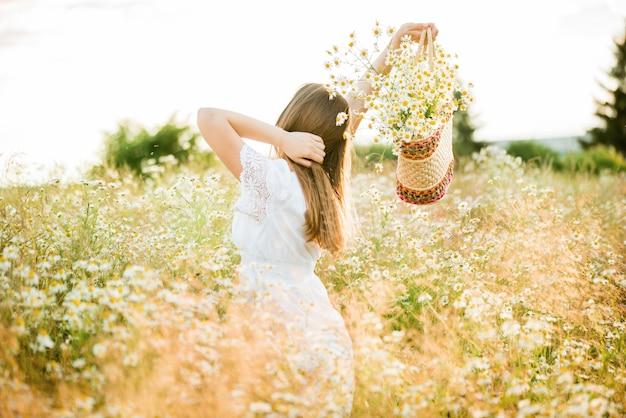 Gelukkig meisje op het veld kamille, zomer zonsondergang. in een witte jurk. rennen en draaien, de wind in mijn haar, levensstijl. vrijheid concept en hete zomer. Premium Foto