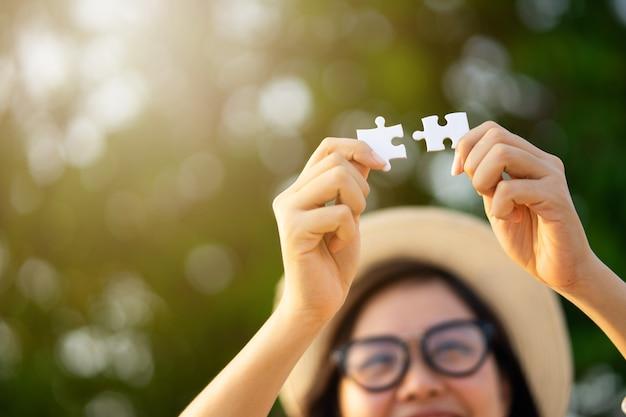 Gelukkig meisje toont twee legpuzzels. liefde compleet. Premium Foto
