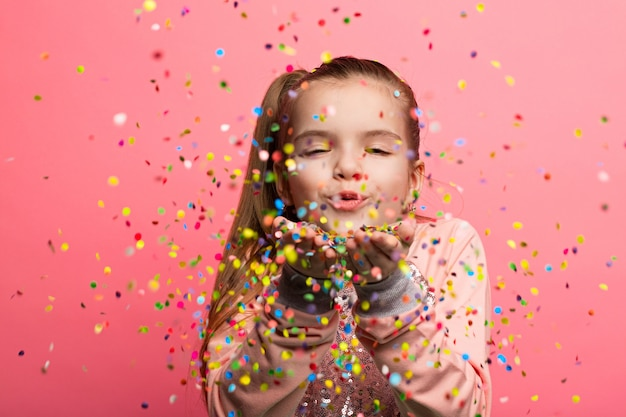 Gelukkig meisje vieren op een roze achtergrond. Premium Foto