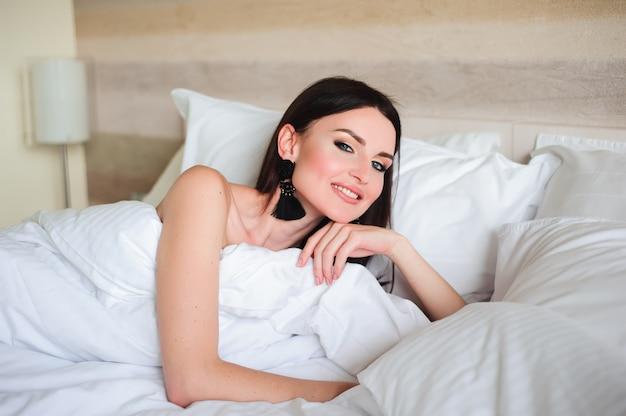 Gelukkig meisje wakker uitrekkende armen op het bed in de ochtend. Premium Foto