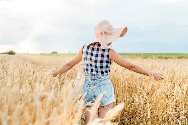 Gelukkig meisje, wandelen in gouden tarwe, met haar rug, buiten levensstijl. vrijheid concept. Premium Foto