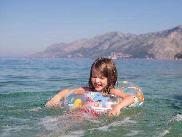 Gelukkig meisje zwemt in een opblaasbare cirkel in de zee, adriatische zee, kroatië Premium Foto