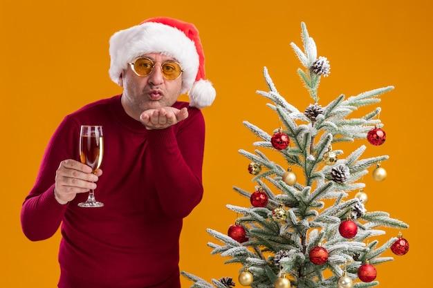 Gelukkig middelbare leeftijd man met kerst kerstmuts in donkerrode coltrui en gele bril met glas champagne blaast een kus staande naast een kerstboom op oranje achtergrond Gratis Foto