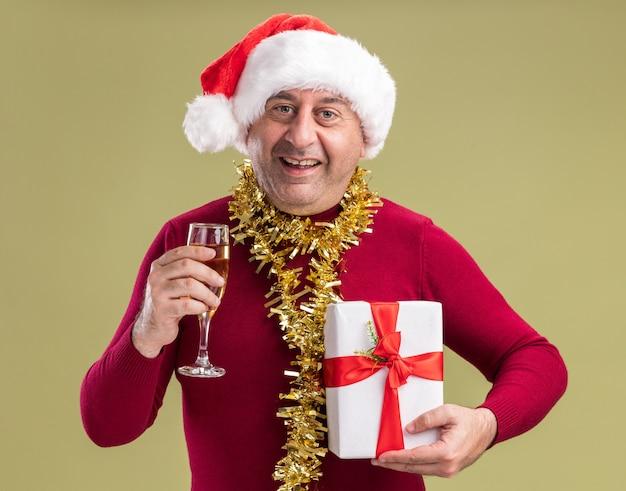 Gelukkig middelbare leeftijd man met kerst kerstmuts met klatergoud rond de nek met kerstcadeau en glas champagne camera kijken met glimlach op gezicht staande over groene achtergrond Gratis Foto