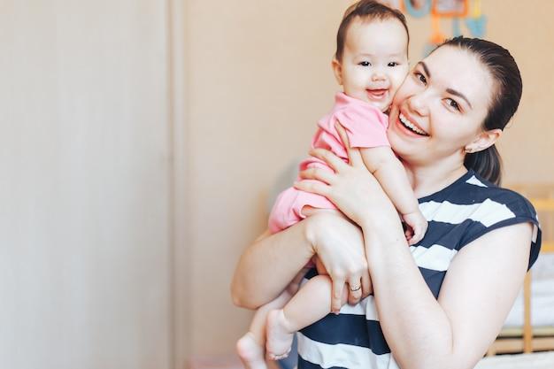 Gelukkig moeder en babymeisje in roze kleren die thuis spelen Premium Foto