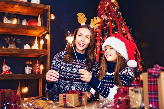 Gelukkig moeder en meisje in de helper van de kerstman met sterretjes in handen Premium Foto