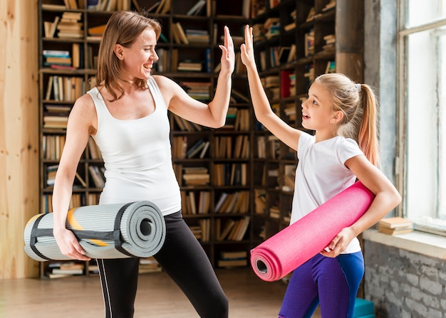 Gelukkig moeder en meisje met yogamatten en high fiving Gratis Foto
