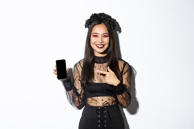 Gelukkig mooi aziatisch meisje in heksenkostuum wijzende vinger op smartphonescherm met tevreden glimlach Gratis Foto