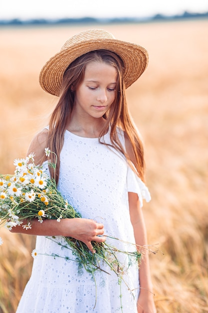 Gelukkig mooi meisje in een tarweveld buitenshuis Premium Foto