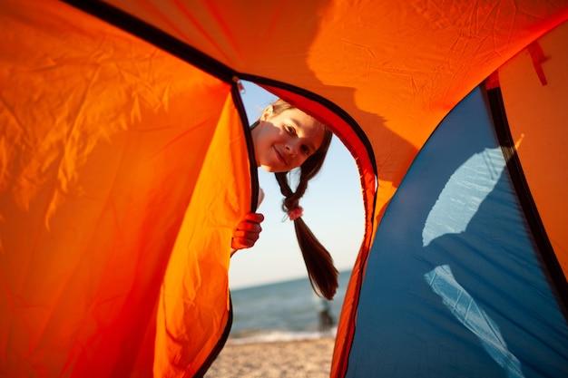 Gelukkig mooi vrolijk jong meisje staat in de buurt van een lichte tent aan de zanderige oever van de blauwe zee en glimlacht kijken naar de camera Premium Foto