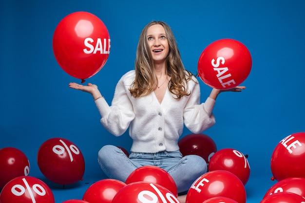 Gelukkig mooie dame die op haar handpalmen twee rode ballonnen met de inscriptie verkoop, geïsoleerd op blauwe muur Premium Foto